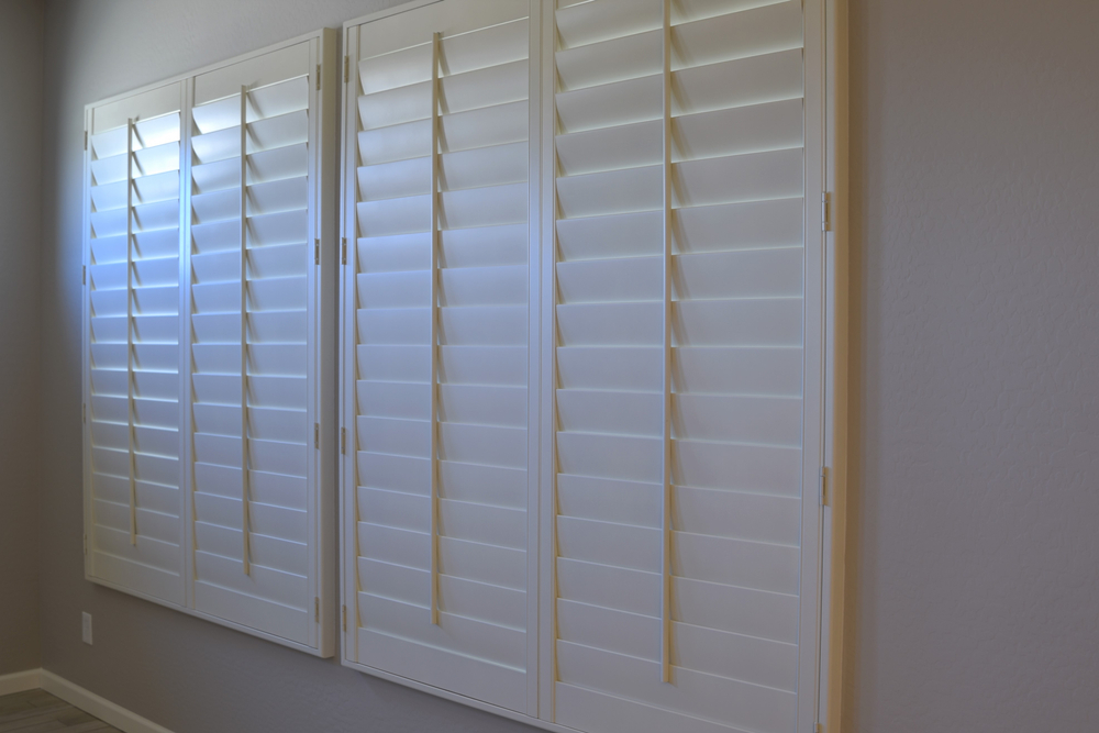A pair of closed plantation shutters in a living room space.