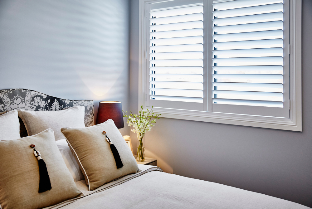 A bedroom with a bed and pillows with a pair of plantation shutters.